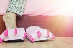 Pés fêmeas em deslizadores cor-de-rosa bonitos do pé do monstro Foto de Stock Royalty Free