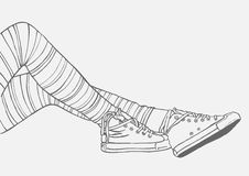 Pés fêmeas em meias e nas sapatilhas listradas Imagens de Stock