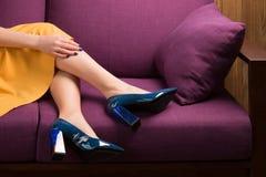 Pés fêmeas em sapatas azuis e na saia amarela A menina está no c fotografia de stock