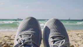Pés fêmeas em sapatas do esporte contra um horizonte de mar video estoque