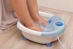Pés fêmeas em um massager de vibração do pé Banho bonde do pé da massagem Cuidado do pedicure e de pé foto de stock royalty free