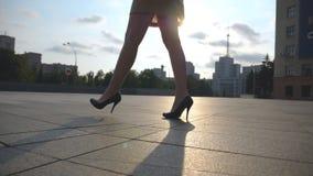 Pés fêmeas magros em sapatas pretas nos saltos altos que andam no quadrado de cidade no por do sol Pés da mulher de negócios nova filme