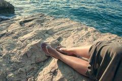 Pés fêmeas na costa rochosa de pedra do mar fotografia de stock