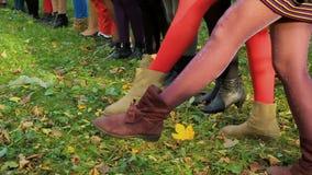 Pés fêmeas na grama Calças justas de cores diferentes nos pés do ` das meninas As meninas levantam acima seus pés nas meias video estoque