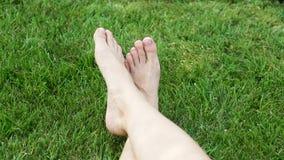 Pés fêmeas na grama verde no parque filme
