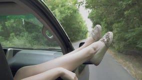 Pés fêmeas na janela de um carro que move sobre os pés das mulheres da estrada que colam fora do passatempo agradável da janela d filme