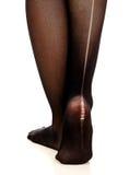 Pés fêmeas na meia-calça rasgada Fotografia de Stock Royalty Free