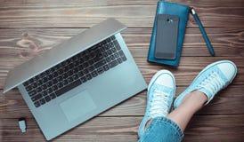Pés fêmeas nas calças de brim e nas sapatilhas, um portátil, um smartphone, uma bolsa em um assoalho de madeira Tecnologias moder imagens de stock royalty free