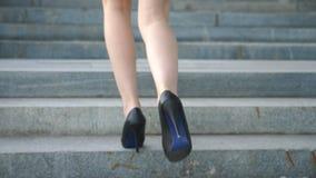 Pés fêmeas nas sapatas dos saltos altos que andam nas escadas Pés da mulher de negócios que intensificam na escadaria Mulher eleg video estoque