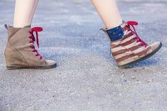 Pés fêmeas nas sapatilhas com o projeto da bandeira americana sobre Fotografia de Stock