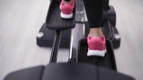 Pés fêmeas nas sapatilhas cor-de-rosa que pedaling em um fim do orbitrek-simulador acima filme