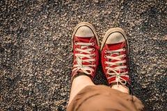 Pés fêmeas nas sapatilhas vermelhas da lona Foto de Stock