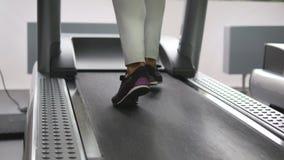 Pés fêmeas que andam e que correm na escada rolante no gym Jovem mulher que exercita durante o cardio- exercício Pés das meninas  filme