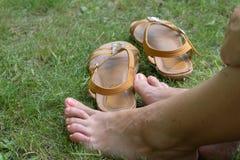 Pés fêmeas que descansam na grama verde Foto de Stock