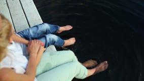 Pés fêmeas que espirram a água na lagoa filme