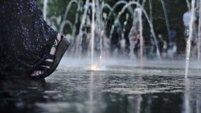 Pés fêmeas que estão entre pulverizadores do fontain do assoalho em uma noite do verão video estoque