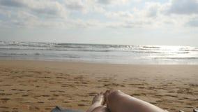 Pés fêmeas que jogam contra o mar Os pés da jovem mulher bonita que relaxam na costa de mar durante férias de verão viajam filme