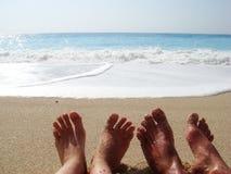 Pés felizes em uma praia arenosa Imagem de Stock