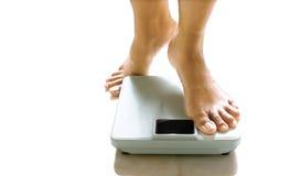 Pés femininos aproximadamente a estar em uma escala de peso. Imagem de Stock Royalty Free