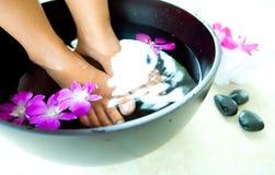 Pés femininos que embebem na bacia de wa scented floral Imagens de Stock
