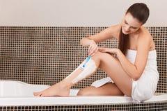 Pés longos da mulher Mulher que barbeia os pés no banheiro Fotos de Stock