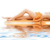 Pés longos de senhora relaxed com toalha alaranjada Fotografia de Stock Royalty Free