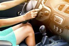 Pés magros bronzeados bonitos do motorista da mulher em um carro Menina no vestido imagens de stock royalty free