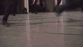 Pés masculinos dos dançarinos que movem sobre o assoalho de dança da fase filme