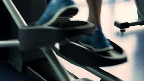 Pés masculinos durante o exercício na máquina elíptica filme