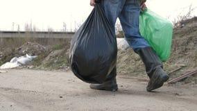 Pés masculinos nas botas que andam na descarga de lixo filme
