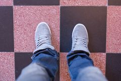 Pés masculinos nas calças de brim e nas sapatilhas na cozinha Fotografia de Stock