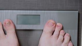 Pés masculinos nas escalas de vidro, a dieta dos homens, peso corporal filme