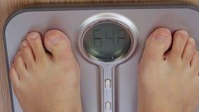 Pés masculinos ou fêmeas que tornam mais pesados na escala eletrônica com zumbir à exposição filme