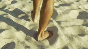 Pés masculinos que andam na areia