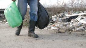 Pés masculinos que andam na descarga de lixo com sacos de lixo filme