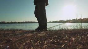 Pés masculinos que andam na luz do sol perto do rio filme