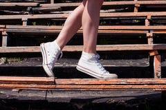 Pés modelo da mulher que vestem as sapatilhas que andam abaixo do banco de velho Imagens de Stock Royalty Free