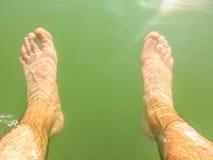 Pés molhados do homem sob a água Foto de Stock