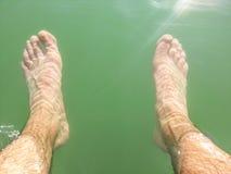 Pés molhados do homem sob a água Foto de Stock Royalty Free