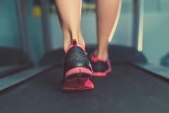 Pés musculares fêmeas nas sapatilhas que correm na escada rolante no gym Conceito para a aptidão, o exercício e o estilo de vida  imagens de stock royalty free