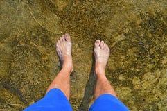 Pés na água pouco profunda sobre rochas imagem de stock royalty free