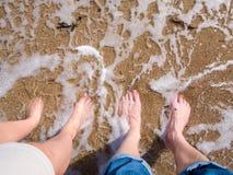 Pés na areia e na água Fotografia de Stock