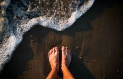 Pés na areia e nas ondas do mar fotografia de stock