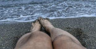 Pés na areia, no mar, e em ondas pretos Fotos de Stock Royalty Free