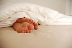 Pés na cama Fotografia de Stock Royalty Free