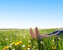 Pés na grama e nas flores da mola Imagens de Stock