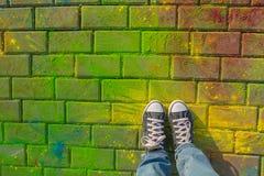 Pés na opinião superior da sapatilha dos jaeans no fundo do holi Foto de Stock