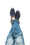 Pés nas calças de brim e botas isoladas no fundo branco Foto de Stock