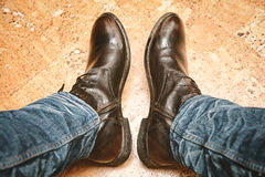 Pés nas calças de brim e nas botas de couro Imagens de Stock Royalty Free