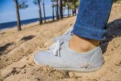 Pés nas calças de brim e nas sapatilhas na areia Fotos de Stock